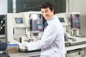 stock photo of urinate  - Portrait of confident male scientist using urine analyzer to test samples in medical lab - JPG