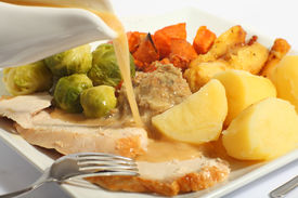 picture of christmas dinner  - Pouring gravy on a festive turkey meal with roast yams roast parsnips boiled potatoes and stuffing - JPG