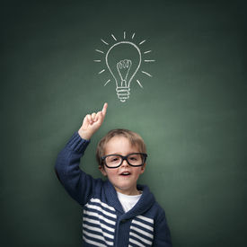 picture of schoolboys  - Schoolboy standing in front of a blackboard with a bright idea light bulb above his head concept for innovation - JPG