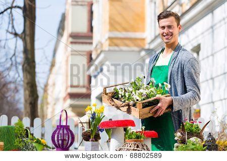 Young handsome florist delivering palette of flowers or viola