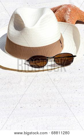Straw Hat And A Seastar On The Beach