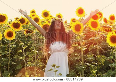 smiling young  woman wearing white dress and wreath of flowers enjoy in summer day in sunflower field , retro colors
