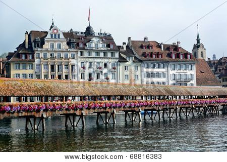 LUCERNE, SWITZERLAND - JULY 2, 2014: Chapel Bridge and Hotels on the Reuss River, Lucerne. The Chapel Bridge spans the Reuss with the Hotel Des Alpes and Mr. Pickwick Pub in background.