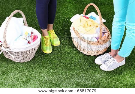 Women near laundry baskets with clean clothes, towels and pins, on green grass background