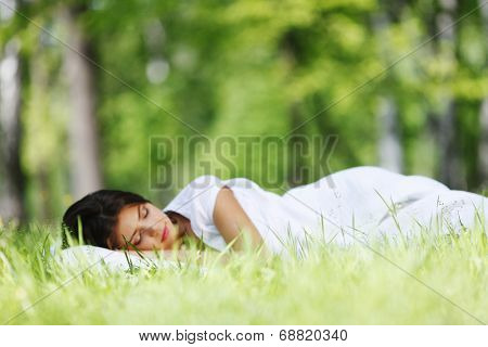 Young woman sleeping on soft pillow in fresh spring grass