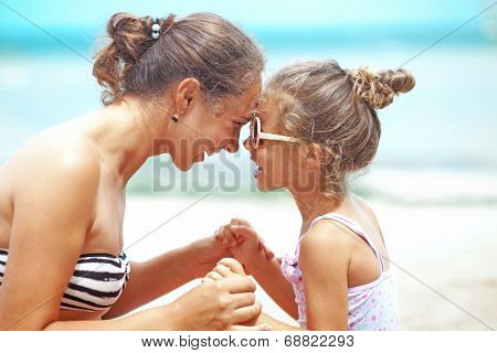 Happy family resting at beach in summer, mother with her 4 years old child