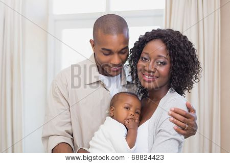 Happy young parents spending time with baby at home in the living room