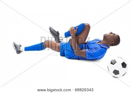 Injured football player lying on the ground on white background