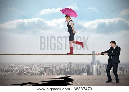 Young business man pulling a tightrope for businesswoman against cracked balcony overlooking city