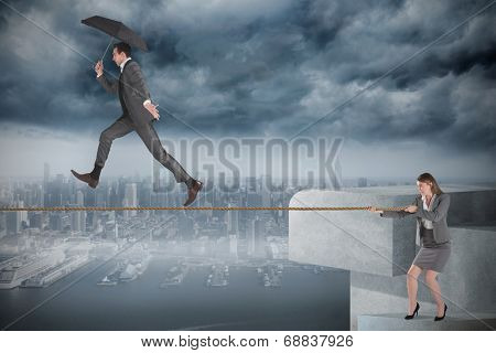 Young businesswoman pulling a tightrope for businessman against coastline and city