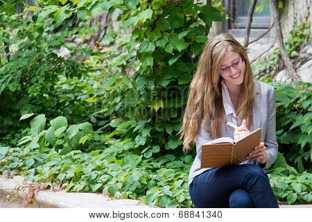 Smiling Woman Writes In Her Journal