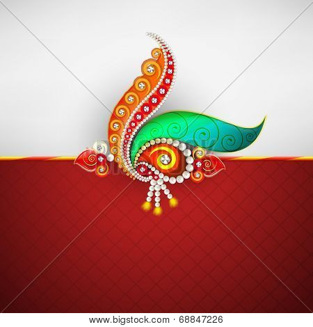 Beautiful peacock feathers and pearls decorated rakhi on grey and red background for Raksha Bandhan celebrations.