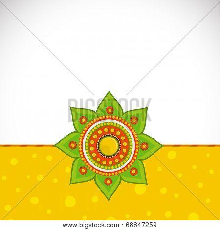 Beautiful rakhi on bright yellow and grey background for Raksha Bandhan celebrations.