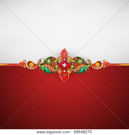 Beautiful rakhi decorated with peacock feathers on red and grey background for Raksha Bandhan celebrations.