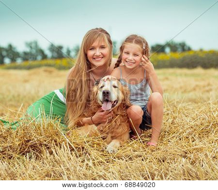 lovely family: mother and daughter with a dog in field