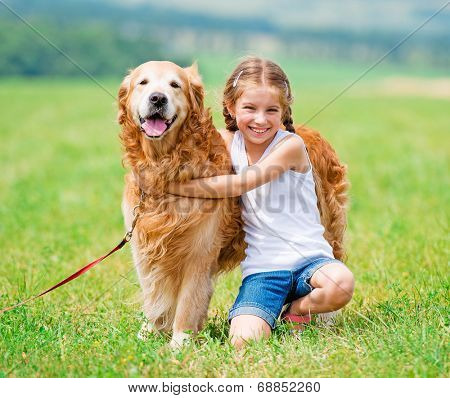 Little girl hugging golden retriever in the summer park
