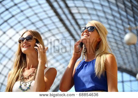 Happy girls with sunglasses taking photos with a smartphone