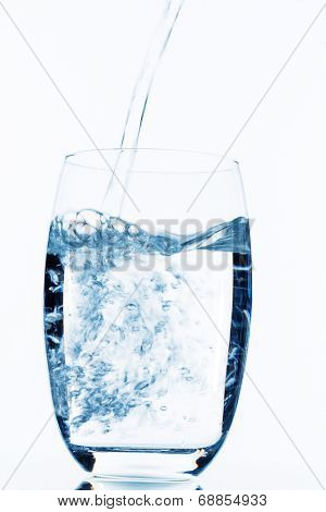 water is poured into a glass, symbol photo for drinking water, freshness, demand and consumption