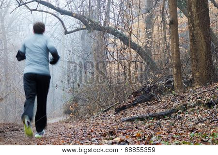 Motion blurred woman running in foggy winter morning