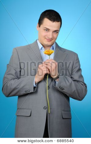 Handsome businessman holding gerber flower
