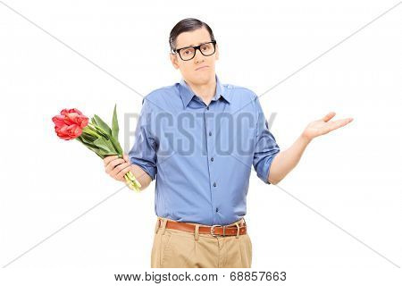 Displeased young man holding a bunch of flowers isolated on white background