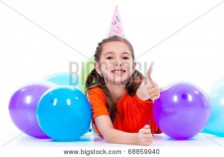 Happy smiling girl in orange t-shirt lying on the floor with colorful balloons and showing thumbs up - isolated on a white.