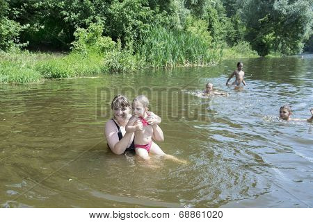 Mother With A Small Daughter Swimming In The River.