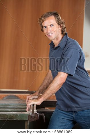 Portrait of confident male carpenter using tablesaw in workshop