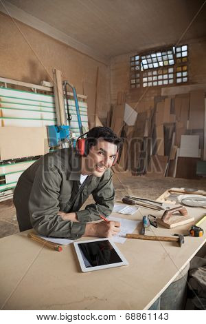 Portrait of handsome carpenter working on blueprint while wearing ear protectors at table in workshop