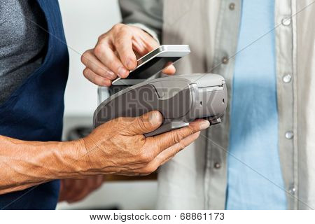 Midsection of salesman accepting payment through NFC technology from customer in hardware store