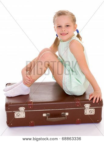 little girl with a big and very old suitcase.