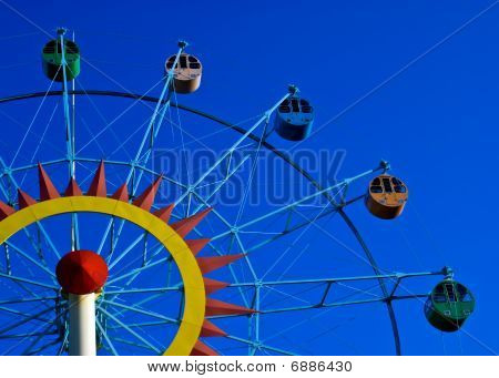 A Colorful Ferris Wheel Shot Against A Blue Sky, Right View