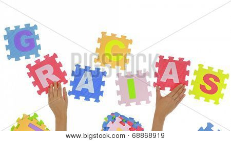 "Hands forming word ""Gracias"" with jigsaw puzzle pieces isolated"