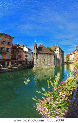 ANNECY, FRANCE - SEPTEMBER 17, 2012: Charming old town of Annecy in Provence. Bastion- prison turned into  museum, is reflected in the water channel. Clear early morning