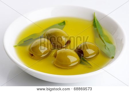 bowl of fresh olive oil with olives and olive leaves
