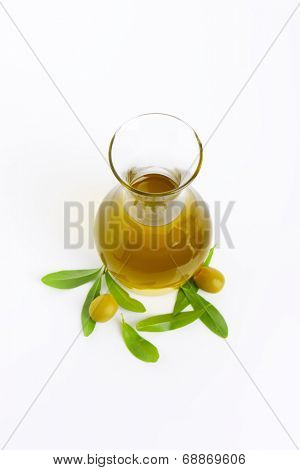 carafe of fresh olive oil, olives and olive leaves on white background