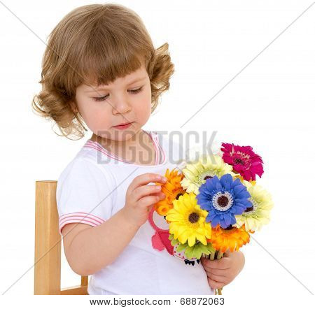 Beautiful little girl with beautiful hairstyle holds a bouquet of flowers