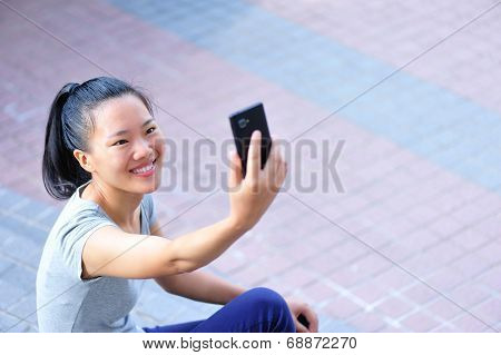 young asian woman sit and use her smart phone taking self photo