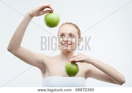 Portrait of young attractive woman holding two green apples