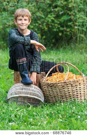 Lad sitting near basket full of chanterelles