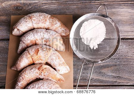 Tasty bagels with sugar powder, on wooden background