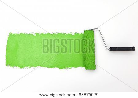 Green paint roller on white background