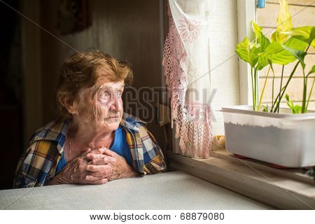 Pensive elderly woman looking out the window.