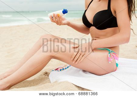 woman is applying sunblock on the beach, vintage-style photo.