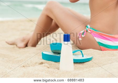 Woman applying sun protection lotion. Bottle of sun protection lotion and flip flops.
