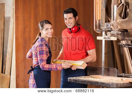 Portrait of happy young carpenters measuring wood together in workshop