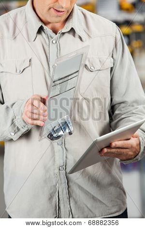 Midsection of male customer scanning product through tablet computer in hardware store
