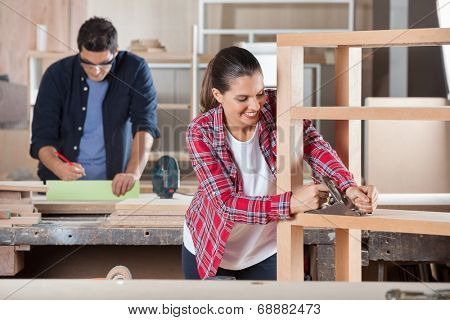 Happy female carpenter shaving wood with planer while colleague working in background at workshop