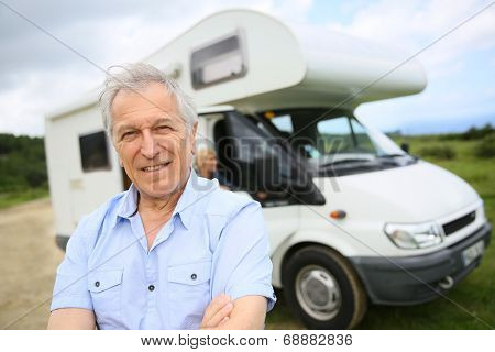 Portrait of happy senior man standing in front of motorhome