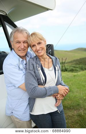 Senior couple standing by motorhome in countryside